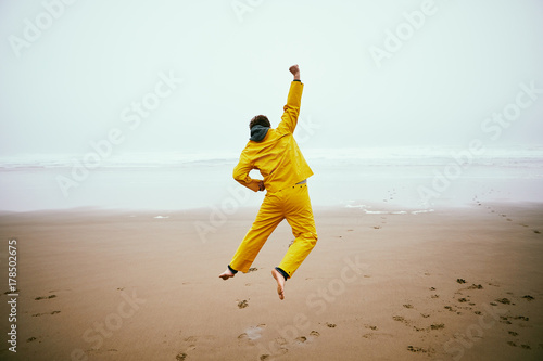 Fotografie, Obraz  excited fisherman on beach jumping with arms raised