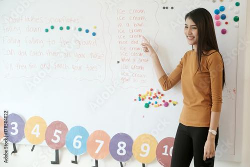 Cuadros en Lienzo Young asian woman teacher teaching english kids in kindergarten classroom, presc