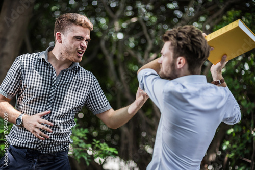 businessman fight and punch in garden business competition concept Canvas Print