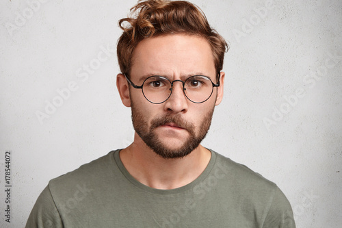 Fotografiet  Puzzled serious irritated angry young unshaven man with beard and mustache curves lips, has sullen expression, being annoyed with girlfriend who betrayed him, sorts out relationships