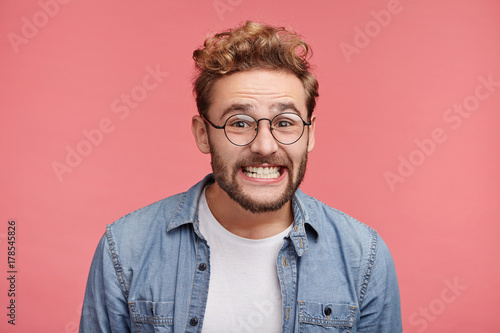 Fotografia  Cheerful bearded man grins at camera, has overjoyed expression, clenches teeth, being glad to be promoted at work and recieves new post