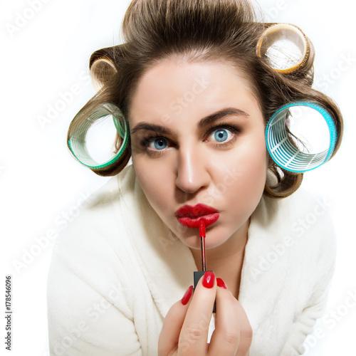 Fotodibond 3D Śmieszny portret błękitnooka kobieta opatrunkowa toga i w curlers pomadce w czerwieni jej wargi patrzeje kamerę jak w lustrze nad białym tłem.