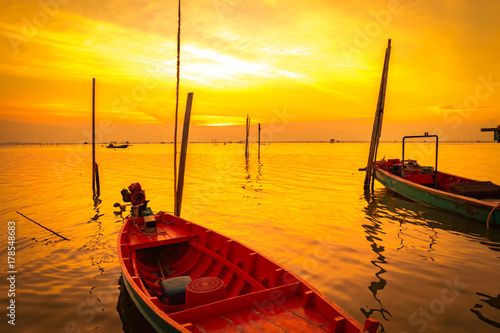 Poster Pleine lune Fisherman's boat floating in the sea near bamboo pole at sunset in Thailand.