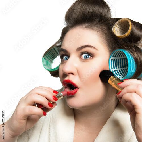 Fotodibond 3D Śmieszny portret błękitnooka kobieta w curlers robi makeup i patrzeje kamerę jak w lustrze nad białym tłem.