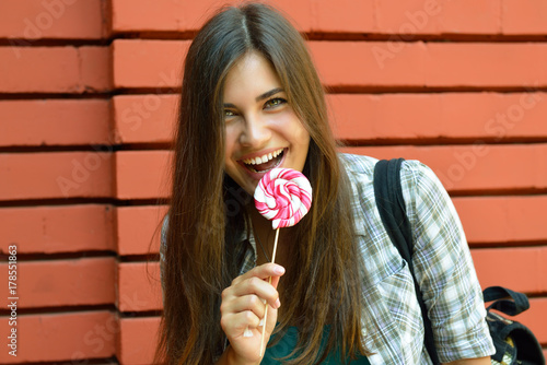Fotografie, Obraz  Beautiful girl has fun and licking sweet candy outdoor against red brick wall