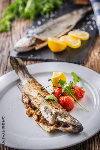 Fototapeta Rybi pstrąg z pieczarkami i warzywem na talerzu w hotelu lub restauraci