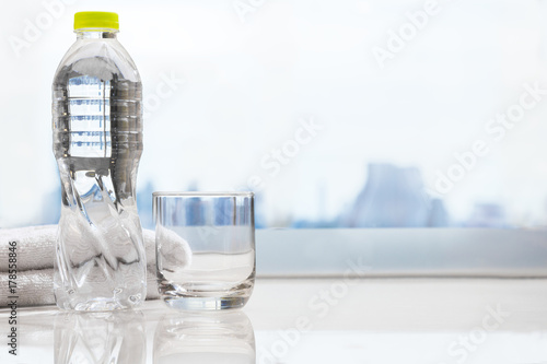 bottle of drinking water and clear drinking glass with white clean
