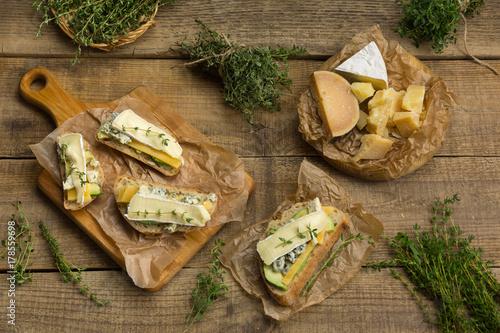 Fototapeta Zdrowe kanapki z awokado, serem i ziołami. Na drewnianym tle.