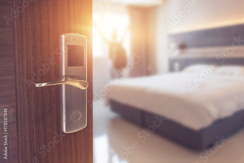Cuadros en Lienzo  Opened door of hotel room in morning with background blurred happy backpacker traveller stay in hotel, sunlight effect