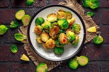 Homemade Roasted Brussel Sprouts With Parmesan Cheese, Lemon, Salt, Pepper On A Old Stone Rustic Table.