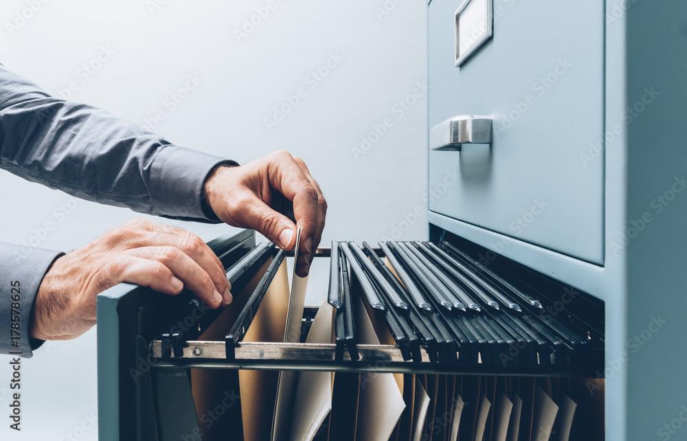 Fototapety, obrazy: Office clerk searching for files