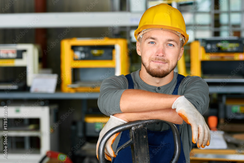 Fototapeta Portrait of cheerful young worker wearing hardhat posing looking at camera and smiling enjoying work at modern factory