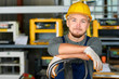 Portrait of cheerful young worker wearing hardhat posing looking at camera and smiling enjoying work at modern factory