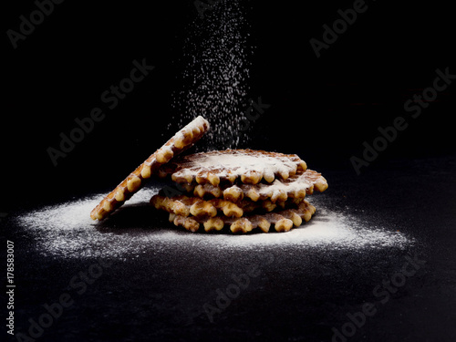 Fotografía  White plate with homemade Belgian waffles, on top of poured sifting of powdered sugar on black background, very tasty snack