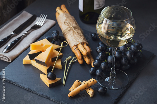 Garden Poster Buffet, Bar Cheese plate served with crackers, grapes and glass of white wine on dark background.