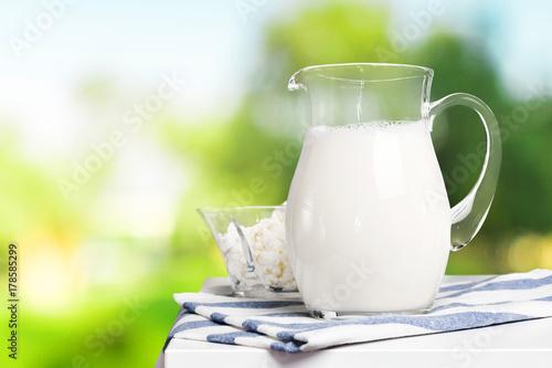 Fototapeta Dzbanek i szklankę mleka na drewnianym stole
