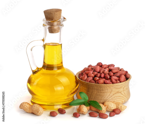 Fototapeta peanut oil in a glass bottle with peanuts in bowl obraz