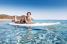 Young Beautiful Woman Relaxing Lying In The Blue Sea On A Sup Board Near Chirali Beach, Turkey