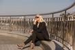 Elegant blonde model posing in black coat, wears sunglasses on a background of city