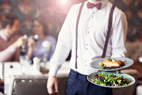 Papiers peints Restaurant Romantic couple dating in restaurant being served by waiter