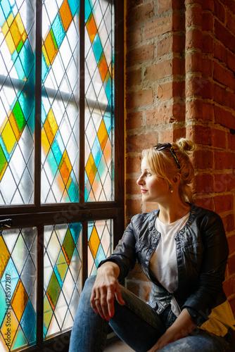 Photo  Blond beautiful woman posing near stained-glass window