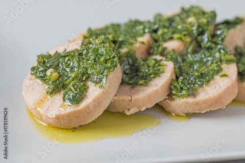 Photo  Homemade tuna meat-loaf with parsley sauce.