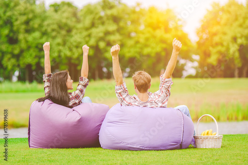 Photo The man and woman sit on the bean bag and gesture