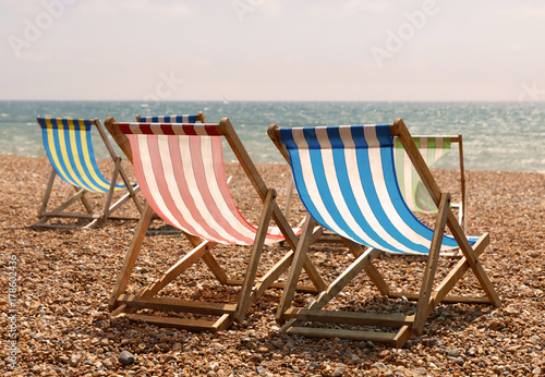 Fototapeta Classic red, blue, green and white striped deckchairs on the beach, the sea in the background in warm evening light obraz
