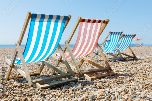 Photo Colorful empty red and blue deckchairs and a parasol on the beach