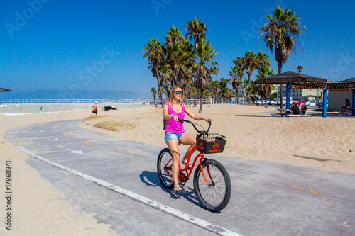 Staande foto Los Angeles Young girl riding a bike by the Muscle beach in Los Angeles, California, USA.