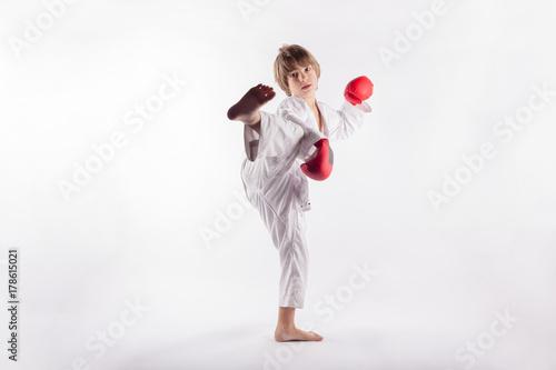 Plakat Chłopiec nosi kimono i czerwone rękawice bokserskie pokazano exercices