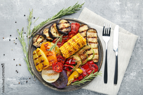 Photo Stands Grill / Barbecue Grilled vegetable on brown cutting board with fork and knife