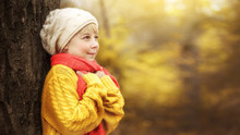 A Little Girl In A Yellow Sweater And A Red Scarf Stands Near A Tree Against The Backdrop Of An Autumnal Forest