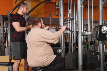 Overweight man with trainer in gym