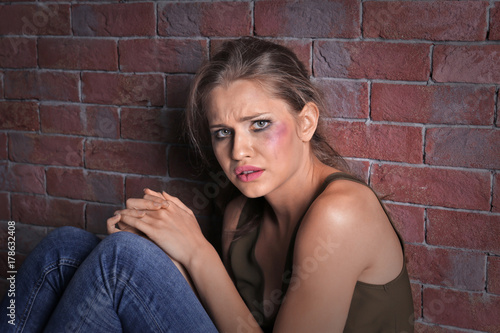 Fényképezés Battered sad woman sitting alone near brick wall