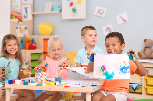 Fotografía  Cute children painting with their palms at table indoor