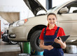 Young female mechanic with clipboard near car in body shop