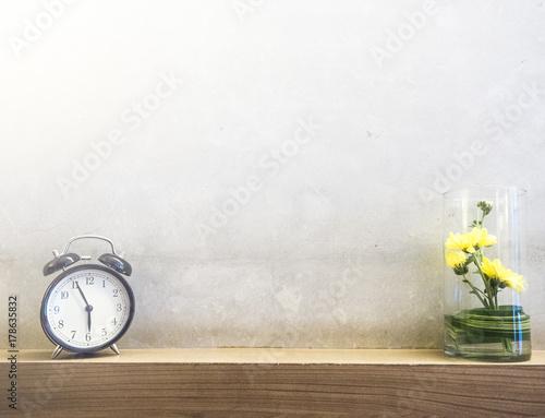 Plakat ranku zegar i żółty kwiat w szkle na stole z cementem izolujemy tło