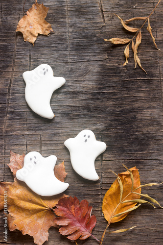 Fotografía  Gingerbread ghost for halloween, decorated with autumn leaves, on a wooden background