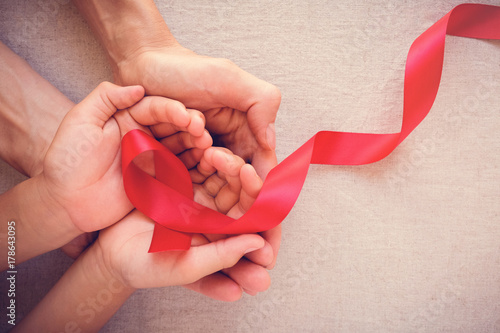 adult and child hands holding red ribbon, hiv awareness concept, world AIDS day Canvas Print