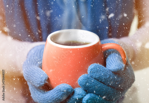 A cup of hot drink, tea or coffee, in winter mittens. Snow falls. New Year concept. Christmas mood.