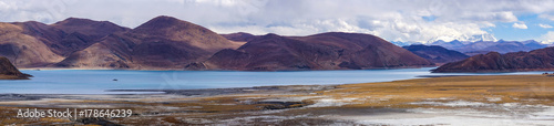Panoramic view of holy lake Yamdrok with snowy mountains in the background- Tibet
