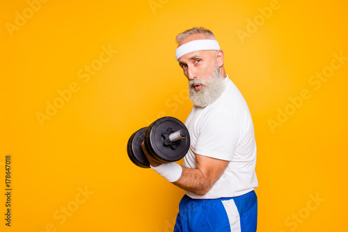 Fotografía  Cool playful flirty naughty strong grandpa with confident grimace exercising holding equipment up, lifts it with strength and power