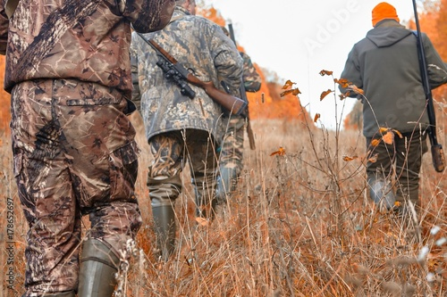 Fotografering group of hunters during hunting in forest