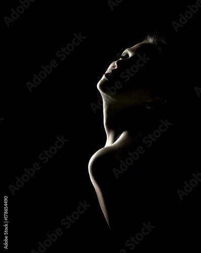 Poster Akt Sensual portrait of woman in shadow on dark background