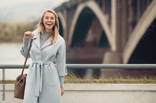 Fotografie, Tablou  Young woman in blue coat. Autumn city background.