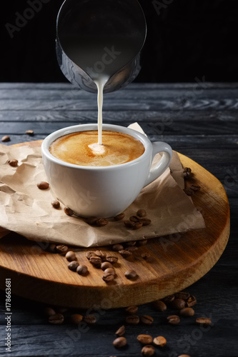 Fotografia  Pouring milk in coffee. Cup with cappuccino on wooden plate