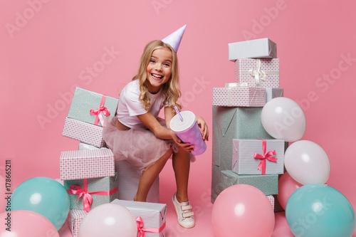 Fototapeta Portrait of a smiling little girl in a birthday hat obraz
