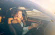 Beautiful businesswoman driving car at sunset