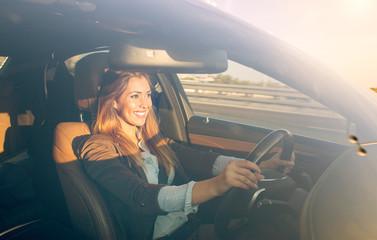 Beautiful businesswoman driving car at sunset